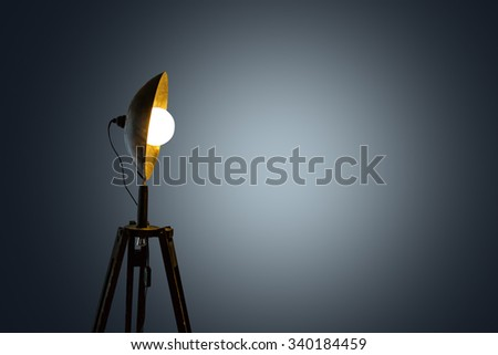 Close up side view of spotlight lighting with bright white bulb, on grey background.