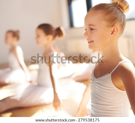 Close up side view of the face of a cute pretty little blond ballerina smiling in class as she practices her poses with her classmates in a warm bright ballet studio - stock photo