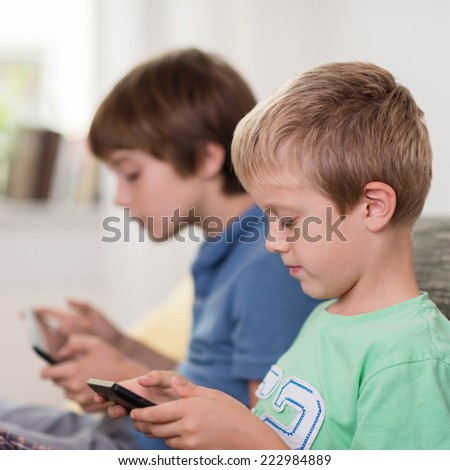 Close up side view of the face of a young boy sitting on a sofa with his brother reading on his tablet computer - stock photo