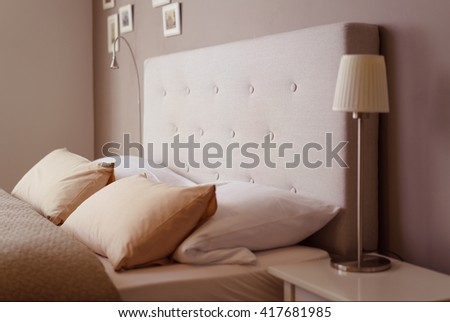Close up side view of the pillows and headboard of an empty double bed with brown and beige linen - stock photo