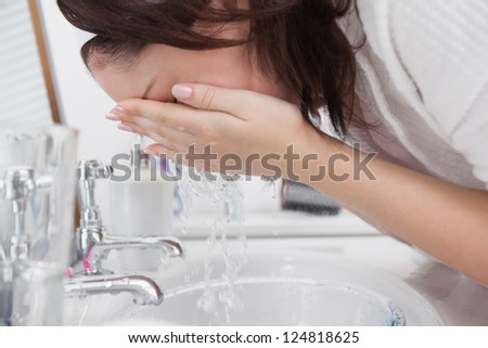 Close-up side view of woman washing face