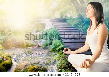 Close up side view of young woman in white meditating next to stream in forest.Girl sitting in wooden path next to water side.