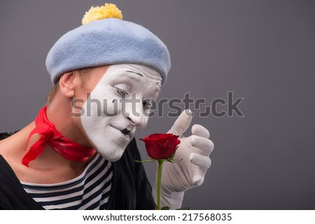 Close-up side-view portrait of young male mime with white face and grey hat holding a red rose and amazed looking at this flower isolated on grey background with copy place - stock photo