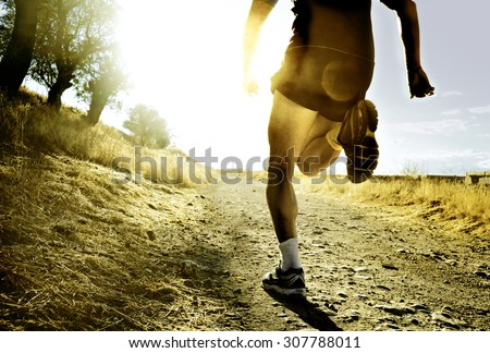 close up silhouette legs and feet of extreme cross country man running and training on rural track jogging at sunset with harsh sunlight and lens flare in countryside sport and healthy lifestyle - stock photo