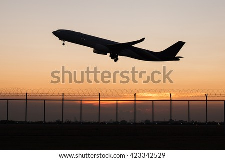 Close up silhouette takeoff plane from the airport while dawn - stock photo