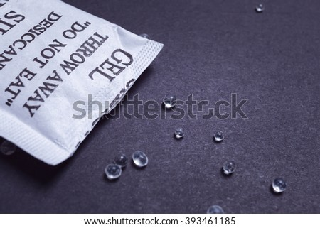Close up silica gel or desiccant in paper bag on black background