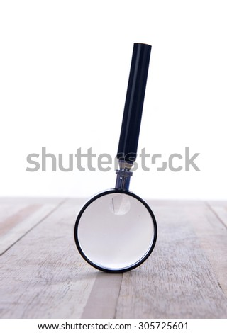 Close up Single Magnifying Glass with Black Handle, Leaning on the Wooden Table. - stock photo