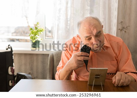 Close up Sitting Elderly Man Shaving Beard with Electric Razor Device at the Wooden Table Inside the House. - stock photo