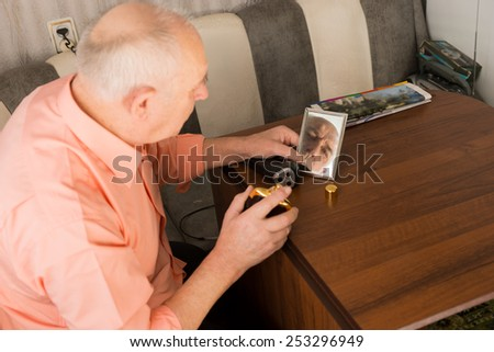 Close up Sitting Old Bald Man with Aftershave Bottle on his Hand Looking at the Small Mirror on Wooden Table. - stock photo