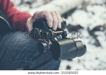 Close up Sitting Old Man Holding a Black Telescope Instrument