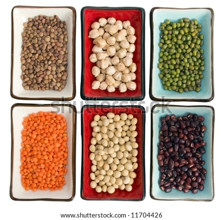 Close up six little dishes with legumes (from left clockwise:small lentils, chickpeas, green beans, azuki beans, soy beans, red lentils). Focus is less intense on the corners. It has a clipping path. - stock photo