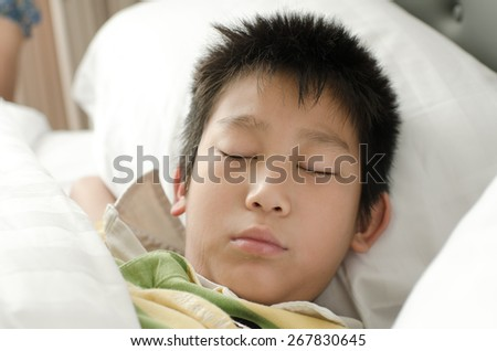 Close up sleeping boy on bed. - stock photo