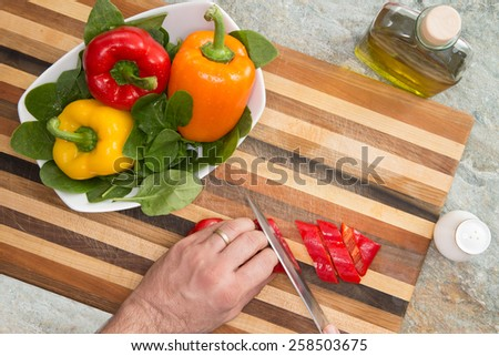 Close up Slicing Fresh Organic Bell Peppers on Top of a Brown Wooden Board - stock photo