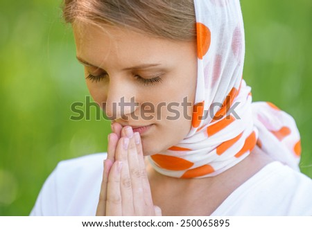 Close-up, small, sad girl in scarf looks down with folded hands near face on green background - stock photo