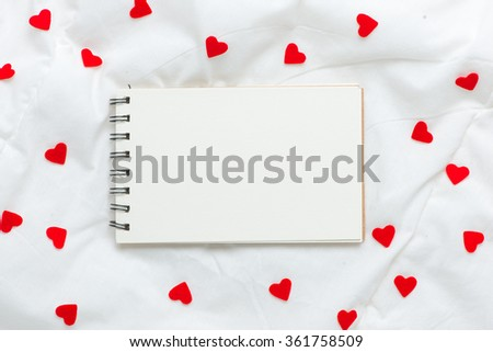 Close up Small White Card with I Love You Message and Red Rose Flower on Top of the white soft silk or blanket. - stock photo