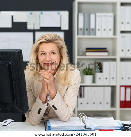 Close up Smiling Adult Office Woman with Blond Hair Sitting at her Work Area with Hands on the Chin. Captured at her Office with Computer and Book on the Table. - stock photo