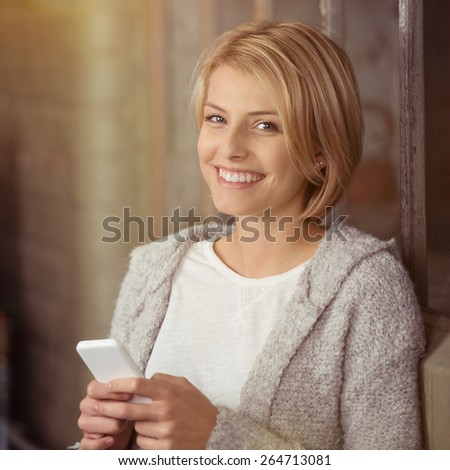Close up Smiling Blond Woman with Gray Knitted Blazer Holding her Mobile Phone While Looking at the Camera. - stock photo