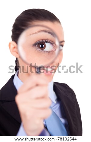 close-up, smiling businesswoman looking through magnifying glass - stock photo