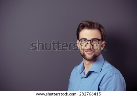 Close up Smiling Good Looking Young Businessman with Eyeglasses Standing Against Gray Wall with Copy Space, Looking at the Camera.