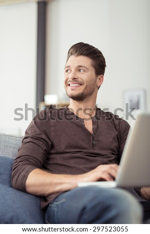 Close up Smiling Handsome Bearded Young Man Holding his Laptop Computer While Relaxing on the Couch and Looking Into the Distance. - stock photo