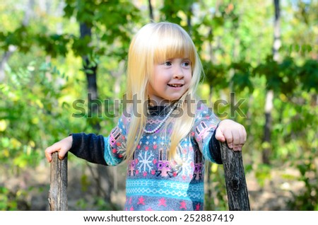 Close up Smiling Little Blond Girl in Autumn Clothing Playing at the Garden. Captured her While Looking Right Frame.