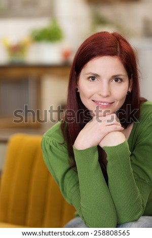 Close up Smiling Pretty Young Woman in Long Sleeve Green Shirt, Sitting on Yellow Couch with Hands on the Chin and Looking at the Camera. - stock photo