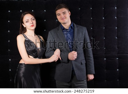 Close up Smiling Young Couple, in Classy Outfits, Looking at Camera on Sparkling Black Background. - stock photo