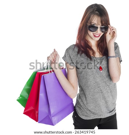 Close up Smiling Young Woman in Casual Outfit Carrying Three Shopping Bags While Peeking Over her Sunglasses. Isolated on White Background. - stock photo