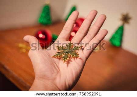 close up snow flake on bare hand with others and christmas decor