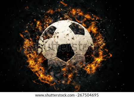 Close-up soccer ball in fire on dark background - stock photo