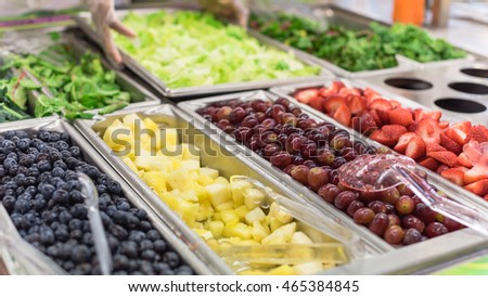 Close-up, soft focus salad bar with various fresh vegetables and fruits. Colorful organic raw slice lettuce, carrot, cucumber, pecan, blueberries, strawberries, grape, dressing. Healthy diet eating.
