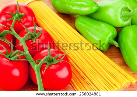 Close-up spaghetti pasta, ripe tomatoes and green peppers on wooden board - stock photo
