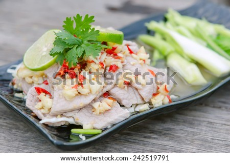 close up spicy pork served with chili sauce , fresh lime on top and fresh kale - stock photo