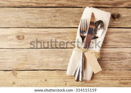 Close up Spoon, Fork and Knife Tied on White Napkin with Empty Tag, on Wooden Table with Text Space. - stock photo