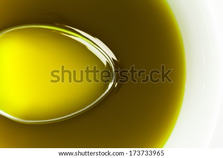Close up Spoon under extra virgin olive oil. - stock photo