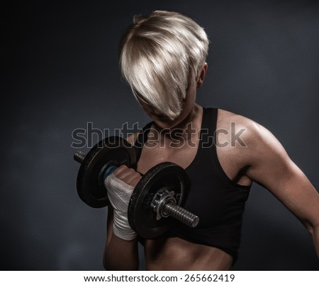 Close up sporty athletic woman ready for hard training with dumbbells on dark background - stock photo