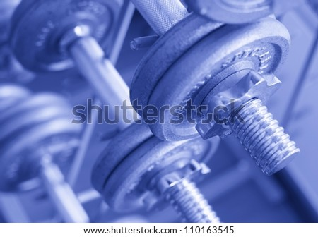 Close up steel dumbells on the pole in sport room - stock photo