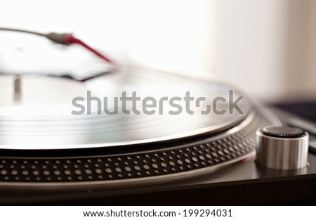 Close up still life detail view of a DJ record player needle touching the groove of the album, playing against a bright light in a music club, interior. Musical hobbies. Equipment at work. - stock photo