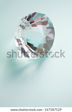 Close up still life detail view of a prism cut gem diamond jewelry piece against a turquoise blue background. Luxury and quality crystal, interior. - stock photo