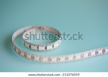 Close up still life detail view of a soft tailor measuring tape laying in a curly shape on a plain blue background, interior. Trade tools and objects for exact measure taking. - stock photo