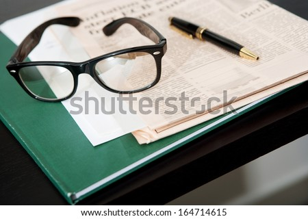 Close up still life of a pair of reading glasses and a black pen laying on an orange financial newspaper and notebook on a dark wooden writing desk. Office interior with no people. - stock photo