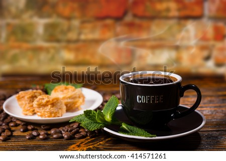 Close Up Still Life of Black Coffee Served in Cup and Saucer Garnished with Fresh Mint Sprigs and Served with Plate of Gourmet Pastries on Wood Table with Roasted Coffee Beans and Rear Brick Wall - stock photo