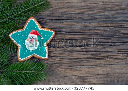 close-up still-life of fir branches and the gingerbread with pattern on magic Christmas holiday on background a wooden boards studio