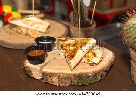 Close Up Still Life of Grilled Quesadilla Appetizer Served on Wooden Cut Tree Trunk Round Served with Two Small Dishes of Salsa and Sour Cream for Dipping - stock photo