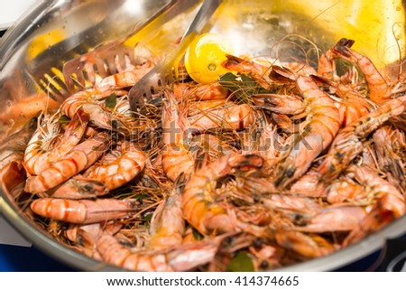 Close Up Still Life of Large Metal Bowl Filled with Cooked Pink Giant Shrimp Prawns Garnished with Lemon, with Tongs at Restaurant Buffet - stock photo