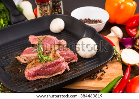 Close Up Still Life of Rare Roast Beef Sizzling in Hot Iron Frying Pan with Fresh Mushrooms and Surrounded by Colorful Vegetables and Seasoning Herbs and Spices - stock photo