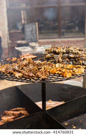 Close Up Still Life of Skewers of Variety of Fresh Seafood and Shellfish Cooking Over Hot Outdoor Grill at Food Festival or Barbecue - stock photo