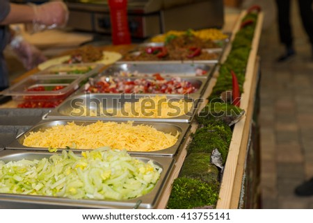 Close Up Still Life of Variety of Garnishes for Mexican Food Chilling in Trays at Food Festival Cart with Person Preparing Tortilla in Background - stock photo