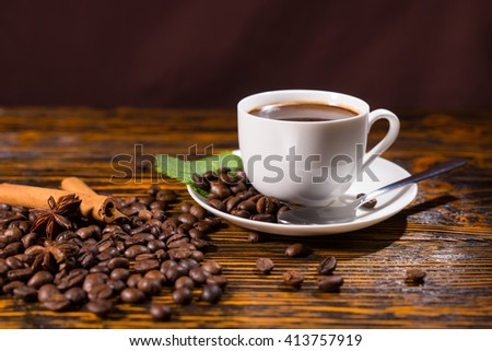Close Up Still Life of White Cup and Saucer Containing Fresh Brewed Coffee Resting on Rustic Wooden Table Top Scattered with Roasted Coffee Beans, Cinnamon Sticks and Star Anise - stock photo