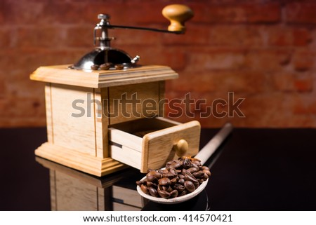 Close Up Still Life of Wooden Spoon Full with Roasted Coffee Beans in front of Traditional Hand Grinder on Shiny Black Reflective Counter with Brick Wall in Background - stock photo